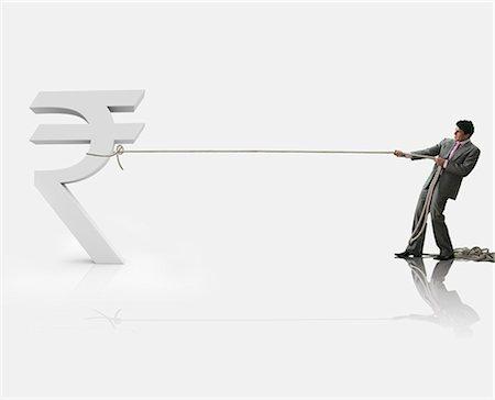 Businessman pulling a rupee symbol Stock Photo - Premium Royalty-Free, Code: 630-06723527