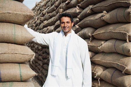 Man standing near stacks of wheat sacks in a warehouse, Anaj Mandi, Sohna, Gurgaon, Haryana, India Stock Photo - Premium Royalty-Free, Code: 630-07071167