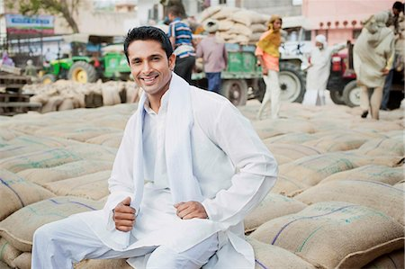 east indian (male) - Man sitting on stack of wheat sacks in a grain market, Anaj Mandi, Sohna, Gurgaon, Haryana, India Stock Photo - Premium Royalty-Free, Code: 630-07071176