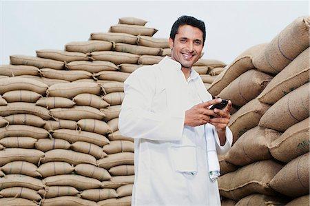 farm phone - Man standing near stacks of wheat sack holding a mobile phone, Anaj Mandi, Sohna, Gurgaon, Haryana, India Stock Photo - Premium Royalty-Free, Code: 630-07071181