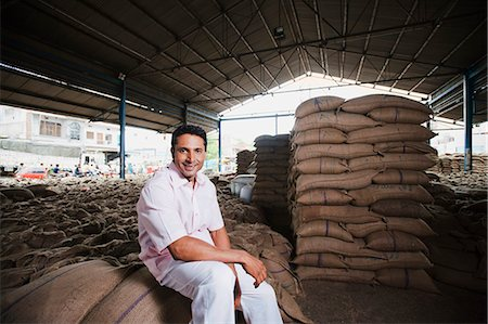 Man sitting on stack of wheat sacks in a warehouse, Anaj Mandi, Sohna, Gurgaon, Haryana, India Stock Photo - Premium Royalty-Free, Code: 630-07071194