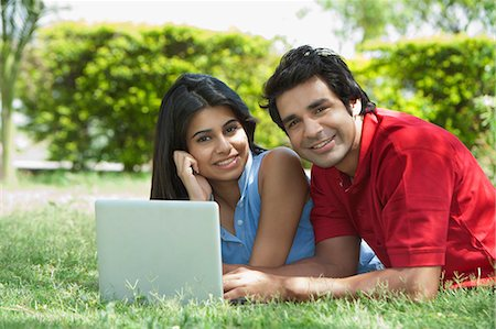 Couple using a laptop in a park, Japanese Park, Rohini, Delhi, India Stock Photo - Premium Royalty-Free, Code: 630-07071228