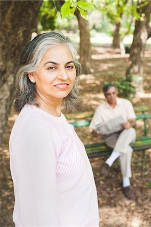 people sitting on bench - Woman leaning against a tree with her husband reading a newspaper in the background, Lodi Gardens, New Delhi, India Stock Photo - Premium Royalty-Free, Code: 630-07071296