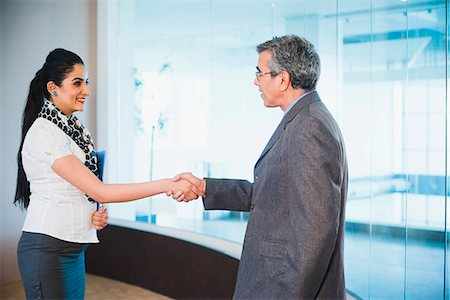 Businessman shaking hands with a businesswoman Stock Photo - Premium Royalty-Free, Code: 630-07071499