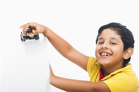 Boy playing with a toy car Stock Photo - Premium Royalty-Free, Code: 630-07071937