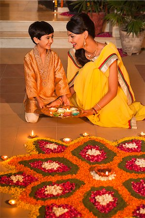 Woman and her son decorating rangoli with oil lamps on Diwali Stock Photo - Premium Royalty-Free, Code: 630-07072014