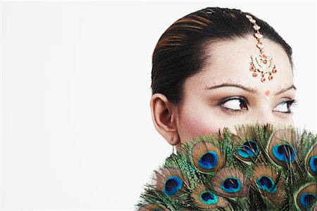 Close-up of a young woman holding a peacock feather fan over her face Stock Photo - Premium Royalty-Free, Code: 630-01127544