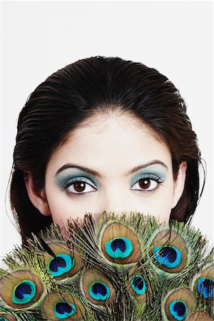 Portrait of a young woman covering her face with a peacock feather fan Stock Photo - Premium Royalty-Free, Code: 630-01129866
