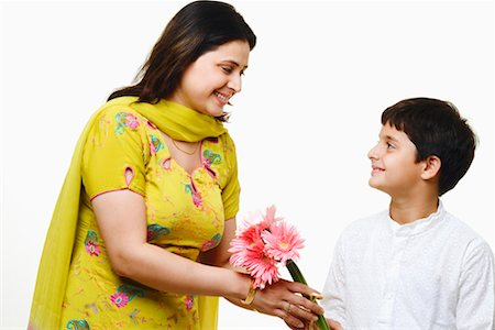 Close-up of a mid adult woman giving a bunch of flowers to her son Stock Photo - Premium Royalty-Free, Code: 630-01297040