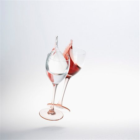 Close-up of wine spilling from two wine glasses Stock Photo - Premium Royalty-Free, Code: 630-01490793
