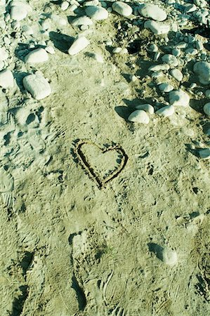 High angle view of heart shape drawn in sand Stock Photo - Premium Royalty-Free, Code: 630-01491127