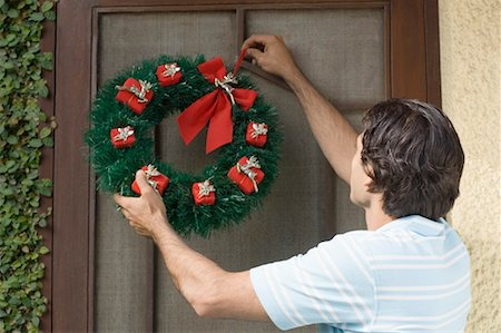 Rear view of a young man hanging wreath on a door Stock Photo - Premium Royalty-Free, Code: 630-01491223