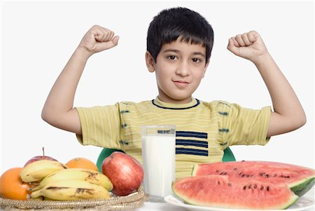 Close-up of a boy sitting in front of food and gesturing Stock Photo - Premium Royalty-Free, Code: 630-01491709