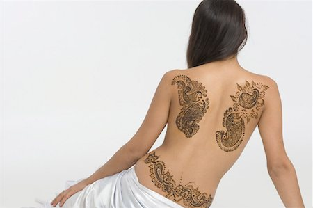 Rear view of a young woman with a tattoo on her back Stock Photo - Premium Royalty-Free, Code: 630-01491755