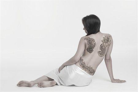 Rear view of a young woman with a tattoo on her back Stock Photo - Premium Royalty-Free, Code: 630-01491756