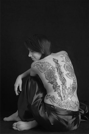 Rear view of a young woman with a tattoo on her back Stock Photo - Premium Royalty-Free, Code: 630-01491764