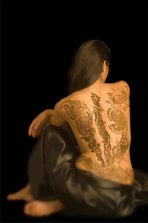 Rear view of a young woman with a tattoo on her back Stock Photo - Premium Royalty-Free, Code: 630-01491765