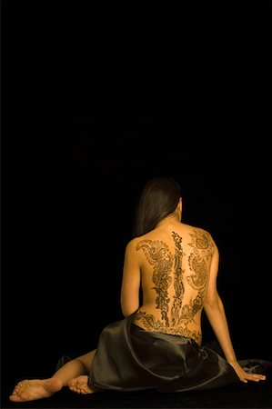 Rear view of a young woman with a tattoo on her back Stock Photo - Premium Royalty-Free, Code: 630-01491766