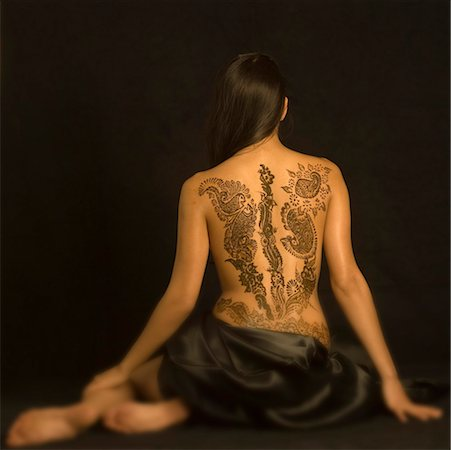 Rear view of a young woman with a tattoo on her back Stock Photo - Premium Royalty-Free, Code: 630-01491767