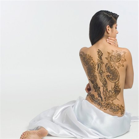 Rear view of a young woman with a tattoo on her back Stock Photo - Premium Royalty-Free, Code: 630-01491768