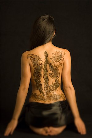 Rear view of a young woman with a tattoo on her back Stock Photo - Premium Royalty-Free, Code: 630-01491760