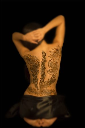 Rear view of a young woman with a tattoo on her back Stock Photo - Premium Royalty-Free, Code: 630-01491761