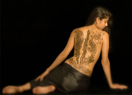 Rear view of a young woman with a tattoo on her back Stock Photo - Premium Royalty-Free, Code: 630-01491763