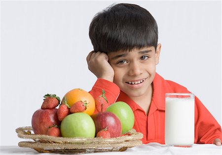 Portrait of a boy making a face in front of a glass of milk and a basket of fruits Stock Photo - Premium Royalty-Free, Code: 630-01491809