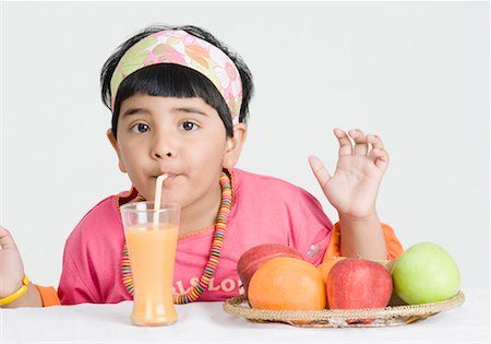 Portrait of a girl drinking juice with a drinking straw Stock Photo - Premium Royalty-Free, Code: 630-01492188