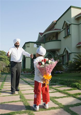 flower greeting - Rear view of a boy hiding a bouquet of flowers standing in front of his father Stock Photo - Premium Royalty-Free, Code: 630-01492650