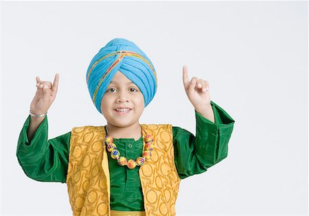 punjabi - Portrait of a boy doing bhangra and smiling Stock Photo - Premium Royalty-Free, Code: 630-01708780