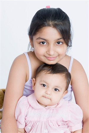 Portrait of a girl sitting with her sister Stock Photo - Premium Royalty-Free, Code: 630-01709155