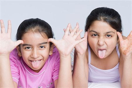 Portrait of two girls making their faces with sticking their tongues out Stock Photo - Premium Royalty-Free, Code: 630-01709152