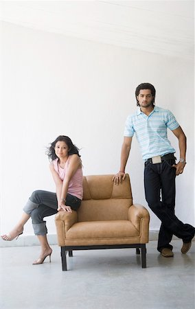 Young woman sitting in an armchair with a young man standing near her Stock Photo - Premium Royalty-Free, Code: 630-01874694
