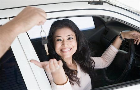 Young woman taking a car key and smiling Stock Photo - Premium Royalty-Free, Code: 630-01874806
