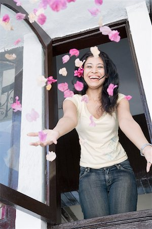 flower greeting - Young woman throwing flowers in air through a window Stock Photo - Premium Royalty-Free, Code: 630-01874834