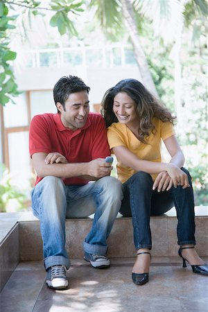 Young man sitting with a young woman and text messaging on a mobile phone Stock Photo - Premium Royalty-Free, Code: 630-01875242