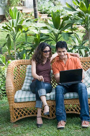 Young man sitting on a couch with a young woman and using a laptop Stock Photo - Premium Royalty-Free, Code: 630-01875296