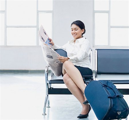 Businesswoman sitting at an airport and reading a newspaper Stock Photo - Premium Royalty-Free, Code: 630-01875854