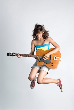 Young woman playing a guitar and jumping Stock Photo - Premium Royalty-Free, Code: 630-01876137