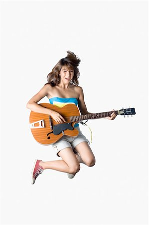 Portrait of a young woman jumping and playing a guitar Stock Photo - Premium Royalty-Free, Code: 630-01876138