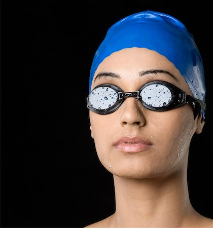 Close-up of a young woman wearing swimming cap and swimming goggles Stock Photo - Premium Royalty-Free, Code: 630-01876543