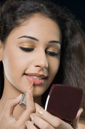 Close-up of a young woman applying lipstick Stock Photo - Premium Royalty-Free, Code: 630-01876560