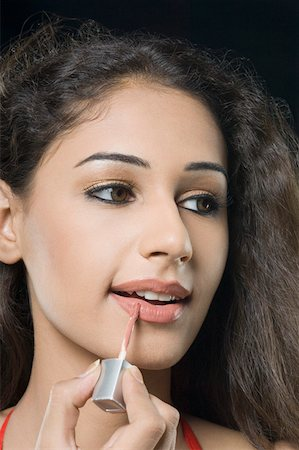 Close-up of a young woman applying lipstick Stock Photo - Premium Royalty-Free, Code: 630-01876561