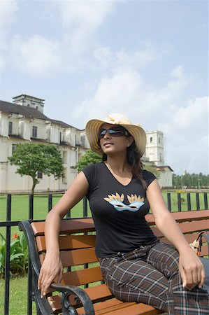 Young woman sitting on a bench with a cathedral in the background, Se Cathedral, Goa, India Stock Photo - Premium Royalty-Free, Code: 630-01876695
