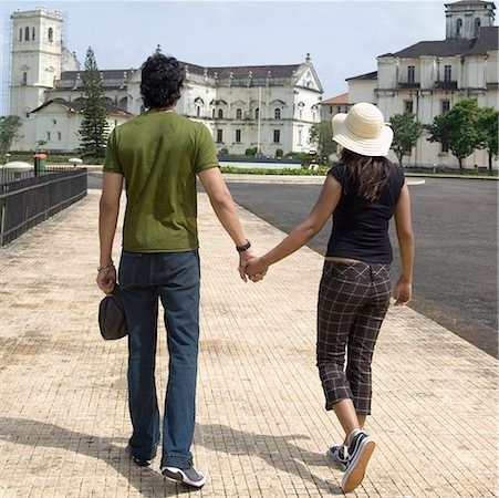 Rear view of a young couple walking with holding hands, Se Cathedral, Goa, India Stock Photo - Premium Royalty-Free, Code: 630-01876690