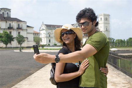 Side profile of a young couple taking a picture of themselves with a mobile phone, Se Cathedral Goa, India Stock Photo - Premium Royalty-Free, Code: 630-01876693