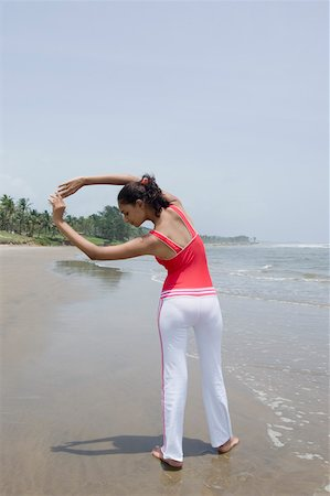 Rear view of a young woman exercising on the beach Stock Photo - Premium Royalty-Free, Code: 630-01876782
