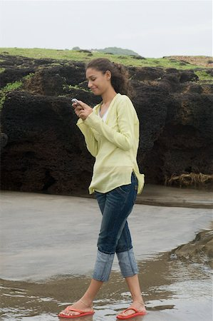 Side profile of a young woman text messaging and smirking on the beach Stock Photo - Premium Royalty-Free, Code: 630-01876870