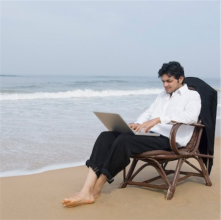 Businessman sitting in an armchair and using a laptop on the beach Stock Photo - Premium Royalty-Free, Code: 630-01877048